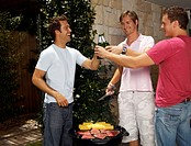 Three young men toasting beer bottles over bbq, smiling