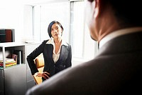 Businesswoman looking at businessman, hand on hip, focus on woman