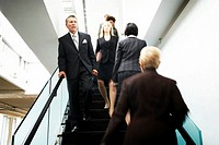 Businessmen and women on stairs, focus on man (blurred motion)