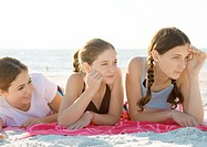 Three preteen girls lying on beach