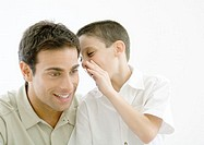 Boy whispering to father