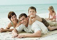 Family lying on beach, smiling