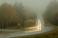 Traffic on road in fog, autumn (long exposure)