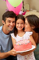Parents kneeling by daughter (5-7) holding birthday cake, smiling