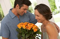 Man giving bouquet of roses to woman, smiling, close-up
