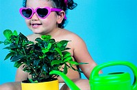 Toddler wearing sunglasses with indoor plant and watering can