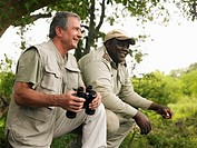 Senior man holding binoculars, on safari with guide, smiling