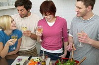 Young men and women drinking white wine and making salad in kitchen
