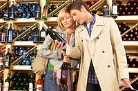 Couple choosing wine in supermarket, smiling