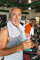 Mature man on machine in gym, holding water bottle, smiling, portrait