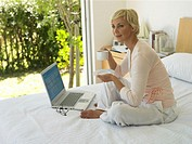Woman sitting on bed holding cup and saucer, open laptop on bed