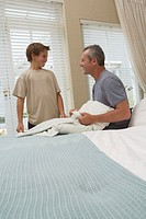 Father and son (9-11) in bedroom, father changing pillow case