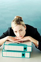 Businesswoman resting her chin on a stack of documents
