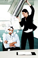 Businesswoman throwing a dustbin of crumpled papers on her colleague