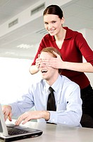 Businesswoman with hands covering her colleague's eyes