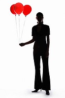 Silhouette of businesswoman holding balloons