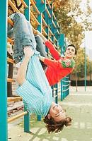 Boys hanging on gymnastic bars.