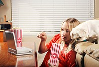 Girl eating popcorn while watching movie on the portable dvd player