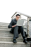 Businessman sitting on the stairs using laptop