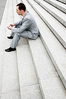 Businessman sitting on the stairs thinking
