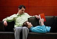 Woman lying on her boyfriend´s lap reading.