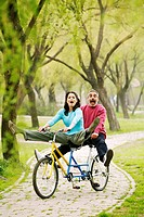 Couple having fun cycling in the park.
