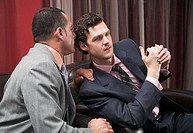 businessman whispering into his friends ear