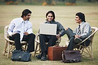 Three businessmen using a laptop