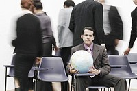 Portrait of a businessman sitting in a meeting holding a globe
