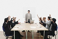 Group of business executives raising their hands at a presentation