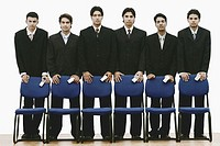 Portrait of a group of young men standing behind chairs holding mobile phones
