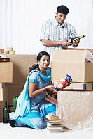 Mid adult couple unpacking cardboard boxes