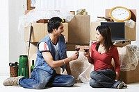 Young couple sitting on the floor holding wineglasses