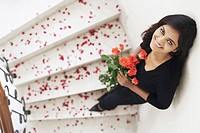 High angle view of a young woman holding a bouquet of flowers