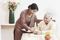 Mature woman serving tea to a mature man