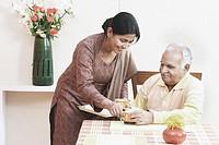 Mature woman serving tea to a mature man