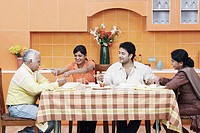 Side profile of a mature couple and their two children at the dining table
