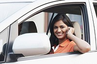 Portrait of a young woman sitting in a car talking on a mobile phone