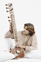 Close-up of a male musician looking at a sitar