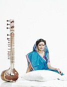 Portrait of a young woman sitting near a sitar (thumbnail)