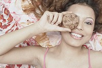 Portrait of a young woman holding a cookie in front of her eye