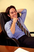 Young businessman sitting in chair and relaxing (thumbnail)