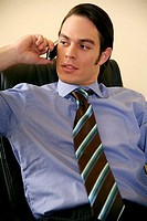 Young businessman sitting and talking on cell phone (thumbnail)
