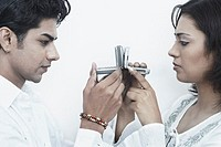 Side profile of a young couple holding mobile phones in front of their faces