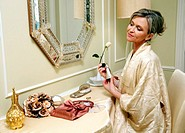 Woman sitting at the dressing table and spraying perfume