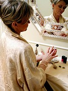 Woman sitting at the dressing table and putting on a ring