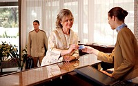 Woman checking in at the hotel reception desk