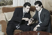 Two businessmen looking at a mobile phone