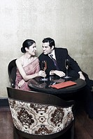 Businessman and a businesswoman sitting on chairs with champagne flutes