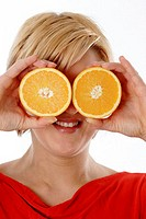 Woman covering her eyes with cut oranges